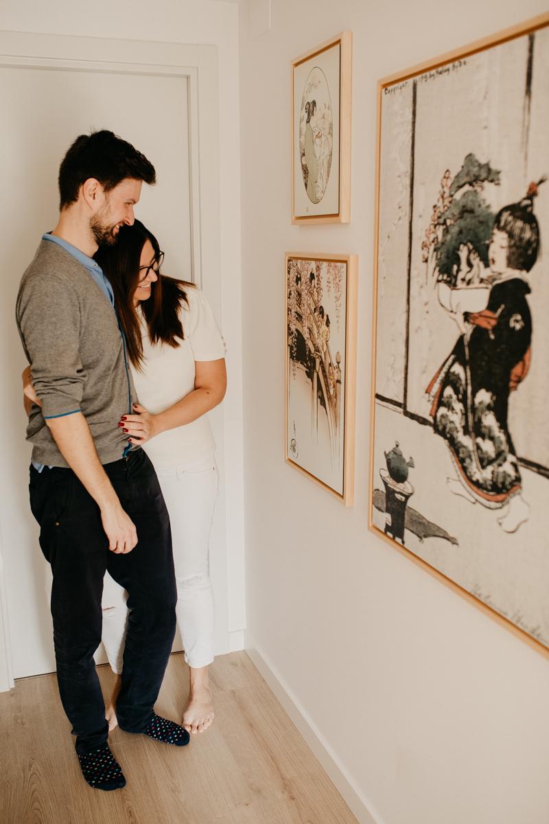 pareja observando una pared decorada con cuadros estilo japandi